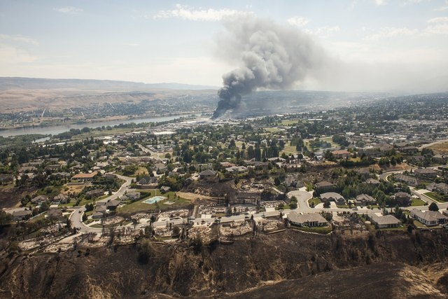 Homes destroyed by the Sleepy Hollow fire are seen as commercial buildings burn in the distance in Wenatchee, Washington June 29, 2015. (REUTERS/David Ryder)