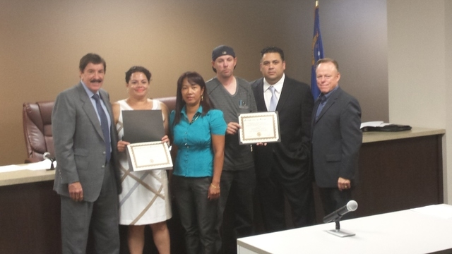 Nellis Cab employees Corazon Nalog and Gregory Janz, center, were recognized at Tuesday's Nevada Taxicab Authority for returning $5,000 to a tourist who accidentally left it behind in the cab driv ...