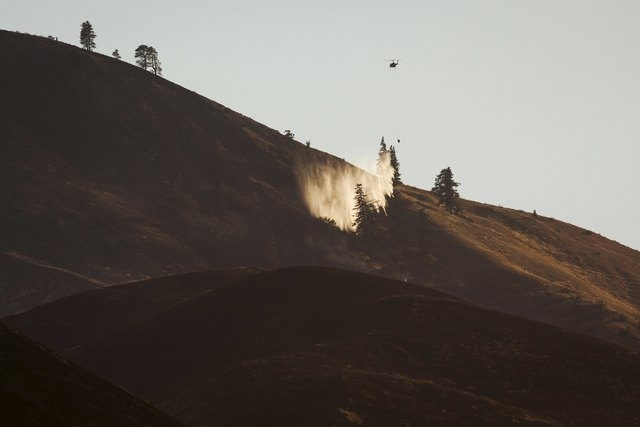 A helicopter drops water onto flames from the Sleepy Hollow fire in Wenatchee, Washington June 29, 2015. A wildfire burning unchecked in Washington state has destroyed at least 23 homes and three  ...