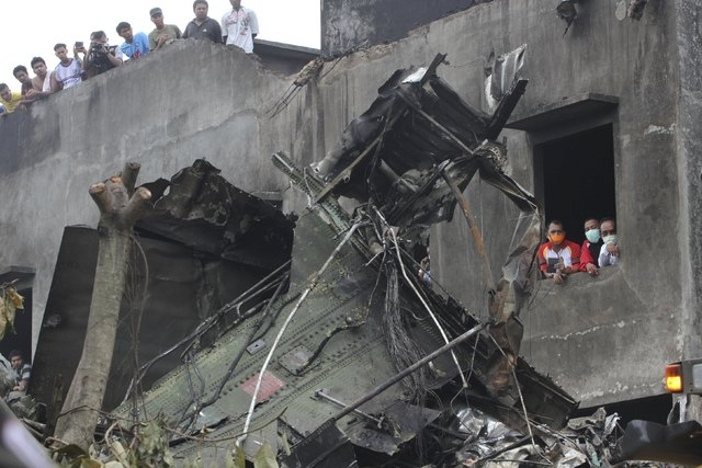 People view the wreckage of an Indonesian military C-130 Hercules transport plane after it crashed into a residential area in the North Sumatra city of Medan, Indonesia, June 30, 2015. More than 1 ...