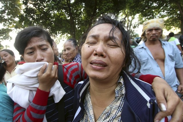 Family members cry outside at Adam Malik hospital as they wait for the bodies of victims of an Indonesian military C-130 Hercules transport plane that crashed into a residential area in the North  ...
