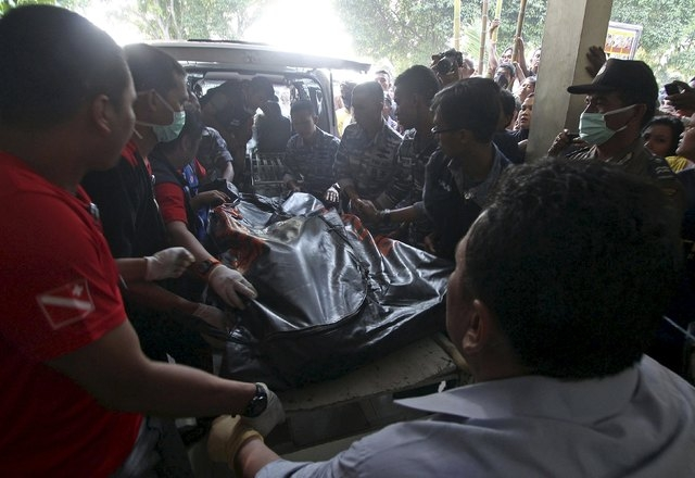 The body of a victim from an Indonesian military C-130 Hercules transport plane that crashed into a residential area, arrives at Adam Malik hospital in the North Sumatra city of Medan, Indonesia,  ...