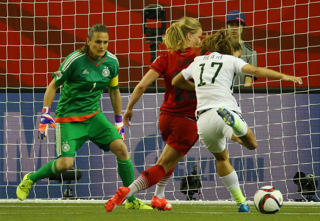 Jun 30, 2015; Montreal, Quebec, CAN; United States midfielder Tobin Heath (17) prepares to take a shot while defended by Germany defender Tabea Kemme (22) as goalkeeper Nadine Angerer (1) looks on ...