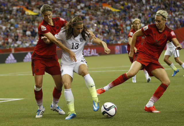 Jun 30, 2015; Montreal, Quebec, CAN; United States forward Alex Morgan (13) goes for the ball against Germany defender Annike Krahn (left) and Germany midfielder Lena Goessling (20) during the fir ...