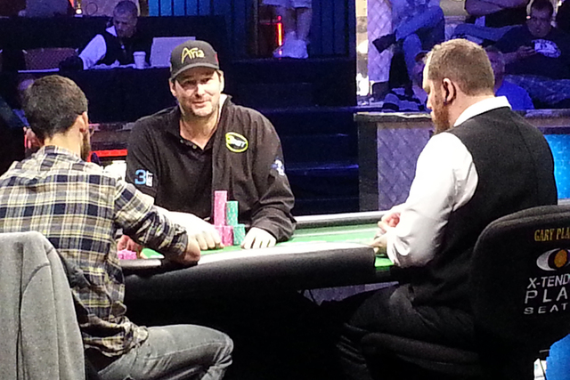 Phil Hellmuth, center, looks at the dealer as opponent Mike Gorodinsky stacks chips during the World Series of Poker's $10,000 buy-in Razz Championship on Monday night at the Rio Convention Center ...