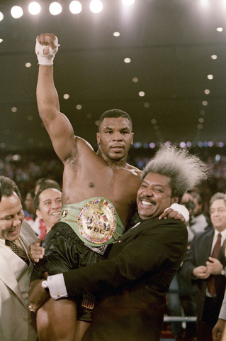 Boxing promoter Don King lifts new heavyweight champion Mike Tyson after Tyson defeated Trevor Berbick in Las Vegas. (AP Photo/Douglas C. Pizac, File)