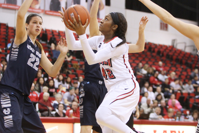 UNLV women's basketball guard Danielle Miller is defended by Utah State forward Tijana Djukic as she drives to the basket during the second half of their Mountain West Conference game Wednesday, F ...