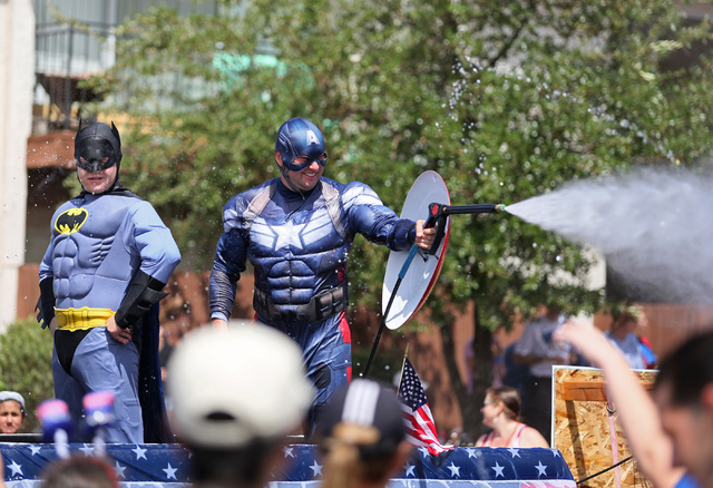 "Men in costumes standing on the Fun and Jump float watch and spray the audience during the 66th Annual Boulder City Damboree Celebration ""Wings of Freedom"" parade Friday, July 4, 2014, in Boulder  ..."