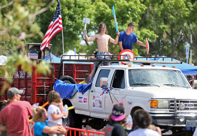 "Men standing on a Zach Of All Trades float participate in a water fight with the audience during the 66th Annual Boulder City Damboree Celebration ""Wings of Freedom"" parade Friday, July 4, 2014, i ..."