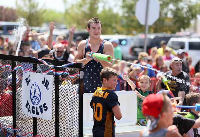 "Trenton Motley, center, sprays the audience with water while riding on the Boulder City Youth Football float during the 66th Annual Boulder City Damboree Celebration ""Wings of Freedom"" parade Frid ..."