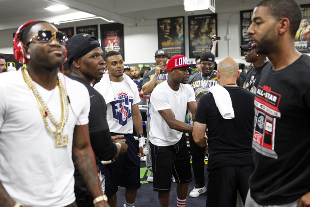 Adrien Broner, left, runs around the ring as Floyd Mayweather speaks with other boxers at the Floyd Mayweather Boxing Club on Wednesday, June 17, 2015, in Las Vegas. Shawn Porter and Adrien Broner ...