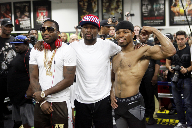 Floyd Mayweather, center, presents Adrien Broner, left, and Shawn Porter at the Floyd Mayweather Boxing Club on Wednesday, June 17, 2015, in Las Vegas. Shawn Porter and Adrien Broner will fight th ...