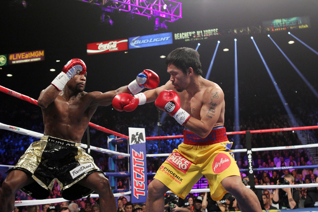 Floyd Mayweather Jr., left, and Manny Pacquiao mix it up in the first round of their welterweight unification boxing match at the MGM Grand Garden Arena in Las Vegas on Saturday, May 2, 2015. (Sam ...