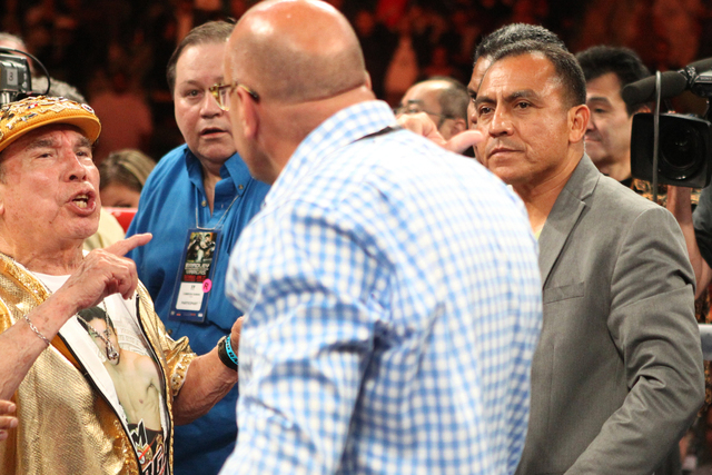Jessie Vargas' cutman Rafael Garcia, left,  and his father Jose Vargas react at the end of his fight against Timothy Bradley Jr. in the interim World Boxing Organization welterweight title match a ...