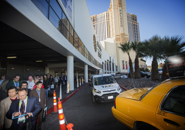 Taxi cabs pass by a line of people waiting for a bus transportation at Sands Expo, 201 Sands Avenue, Wednesday, Jan. 7, 2015 during Consumer Electronic Show.  (Jeff Scheid/Las Vegas Review-Journal)