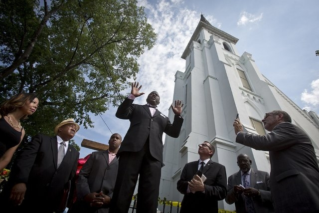 Pastor Dexter Easley of South Carolina leads others in prayer during an impromptu prayer service outside the Emanuel African Methodist Episcopal Church where a mass shooting took place in Charlest ...
