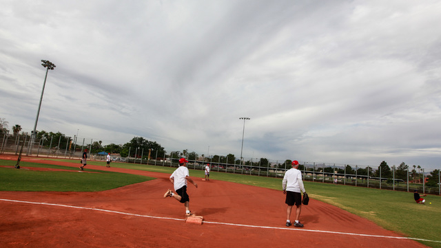 Bobby Castiglione, center left, passes by first base on his way to scoring a run during the Flag Day Celebration Classic by members of the Las Vegas Senior Softball Association at Lorenzi Park in  ...