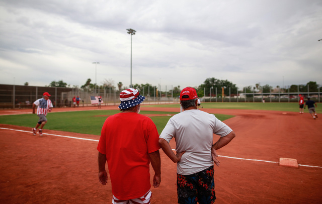Wayne Callahan, left, and George Fernandes watch the action during the Flag Day Celebration Classic by members of the Las Vegas Senior Softball Association at Lorenzi Park in Las Vegas on Tuesday, ...