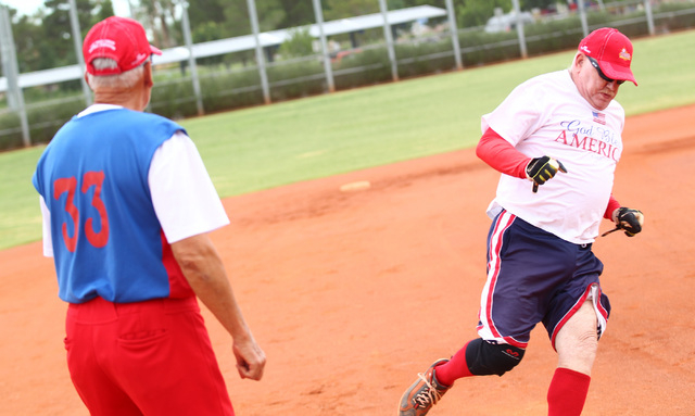 Joe Pellegrino, right, passes by third base to score a run during the Flag Day Celebration Classic by members of the Las Vegas Senior Softball Association at Lorenzi Park in Las Vegas on Tuesday,  ...