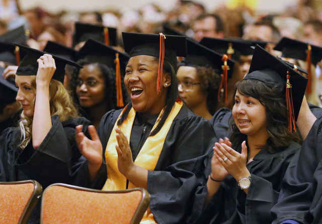 Nevada Virtual Academy high school graduates Karla Tuck, center, and Tiffany Valdez, right, applaud after receiving their diplomas during the class of 2015 commencement ceremony at Aliante hotel-c ...
