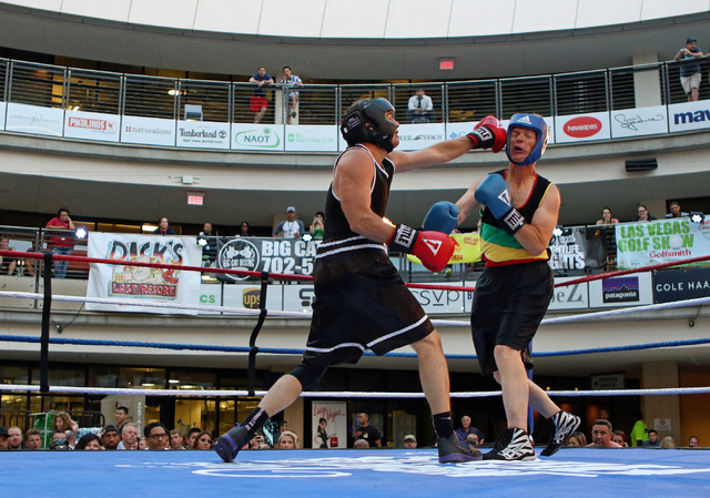 Steve Cyr, left, lands a left during a bout against Ed Powell in the Downtown Throwdown at Zappos headquarters Tuesday, June 9, 2015, in Las Vegas. Bouts included matchups of local fighters and co ...