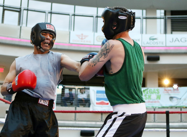 Adolfo Castaneda, left, throws a punch at his opponent Dylan Wiesenthal during the Downtown Throwdown event at Zappos headquarters Tuesday, June 9, 2015, in Las Vegas. Bouts included matchups of l ...