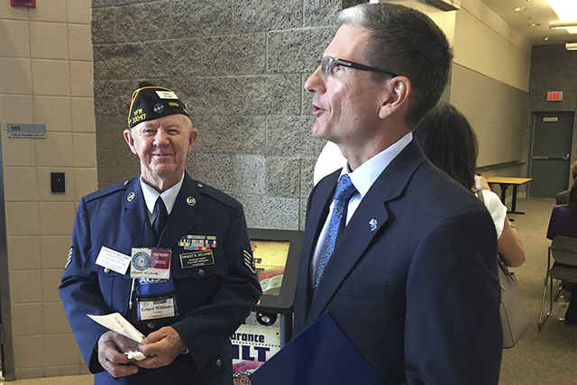 Cold War veteran Ernie Williams, left, listens to Rep. Joe Heck, R-Nev., talk about the Nevada National Security Site before a National Day of Remembrance ceremony Oct. 31, 2014, at the National A ...