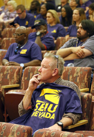 Robert Conway, front, and Service Employees International Union Local 1107 members and supporters wearing purple shirts wait for public comment to take place during the County Commission meeting a ...