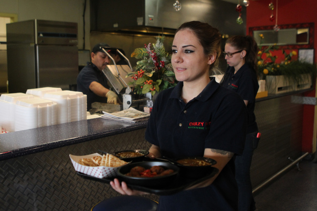 Salina Gallegos delivers food to a table at Crazy Pita Rotisserie and Grill, 2225 Village Walk Drive, in Henderson Monday, Dec. 15, 2014. (Erik Verduzco/Las Vegas Review-Journal)