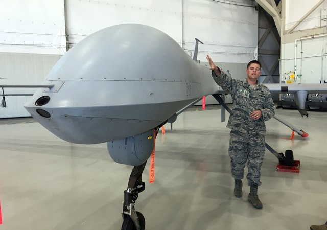 Capt. Will, a maintenance officer, pats the fuselage of an MQ-1B Predator aircraft inside a hangar Tuesday, June 16, 2015, at Creech Air Force Base. Certain personnel involved with remotely pilote ...