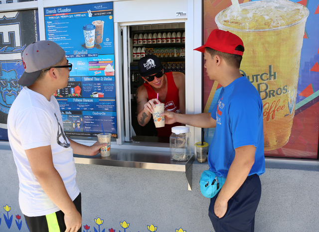 Tan Ngu, right, receives his free drinks from Ryan Vergas, center, as Doug Nguyen looks on at Dutch Bros. coffee shop on 2820 E. Tropicana Ave. Thursday, June 18, 2015. Dutch Bros. coffee shop, wh ...