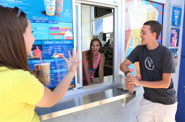 Lidia Penn, left, chats, after receiving her free drinks, with Dutch Bros. coffee shop co-owner, Kelli Gillespie, center, as her husband Andrew Penn looks on Thursday, June 18, 2015. Dutch Bros. c ...