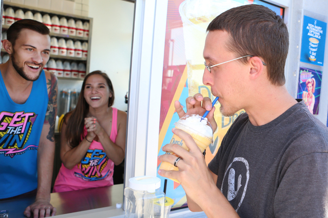 Andrew Penn, right, tests his free drinks as Dutch Bros. coffee shop co-owners, Kelli Gillespie, center, and her husband Cory Nimmer, look on Thursday, June 18, 2015. Dutch Bros. coffee shop at 28 ...
