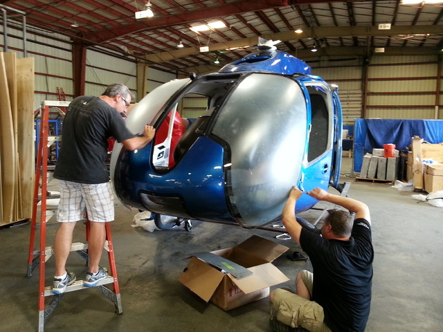 "The crew from Las Vegas company Scroggins Aviation works on a Eurocopter EC-130 that can currently be seen in the blockbuster ""Jurassic World."" (Courtesy/Scroggins Aviation)"