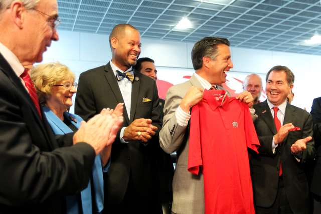 Governor Brian Sandoval reacts to a gift from the UNLV President Len Jessup at UNLV on Thursday, June 10, 2015, in Las Vegas. The bill provides funds for UNLV's law, medical, business and hotel sc ...
