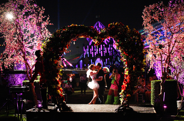 Raul Chapa kisses Victoria Rodriguez, both of La Joya, Texas, at the end of their wedding ceremony at Electric Daisy Carnival at the Las Vegas Motor Speedway in Las Vegas during the early hours of ...
