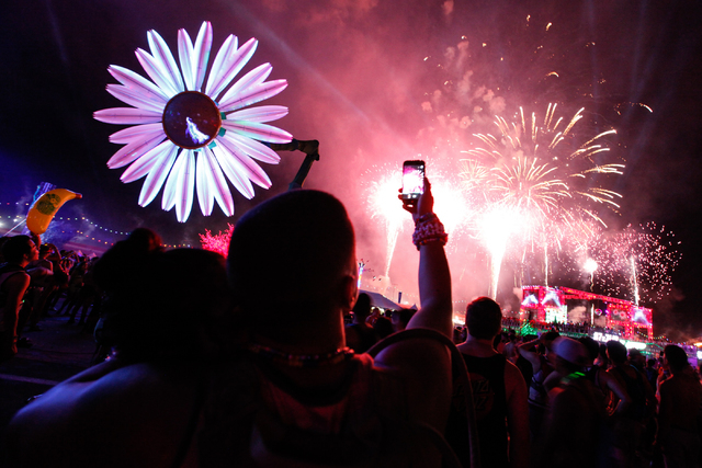 Andrea Plascencia of Corona, Calif., and Sergio Grajeda of Avenal, Calif., watch and record a video of the fireworks display at Electric Daisy Carnival at the Las Vegas Motor Speedway in Las Vegas ...