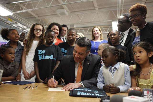 Gov. Brian Sandoval signs SB432 at Matt Kelly Elementary on Wednesday, June 3, 2015, in Las Vegas. The New Victory Schools program gives extra money to Nevada's poorest schools. (James Tensuan/Las ...