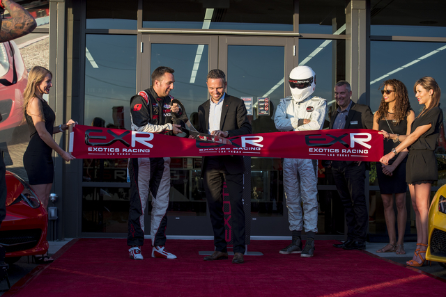 Romain Thievin uses giant scissors as David Perisset holds the ribbon at Exotics Racing during the grand opening at Las Vegas Motor Speedway in Las Vegas on June 4, 2015. Thievin and Perisset are  ...