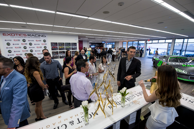 Invited guests receive complimentary champagne at Exotics Racing during the grand opening of the new welcome center at Las Vegas Motor Speedway in Las Vegas on Thursday, June 4, 2015. (Joshua Dahl ...