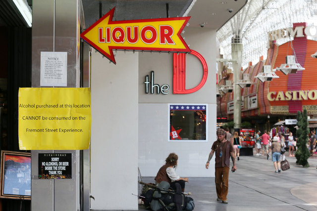 Signs are posted at the entrance to a gift shop that sells liquor at Fremont Street Experience, July 17, 2014, in Las Vegas. A series of liquor ordinances are in effect regulating alcohol carrying ...