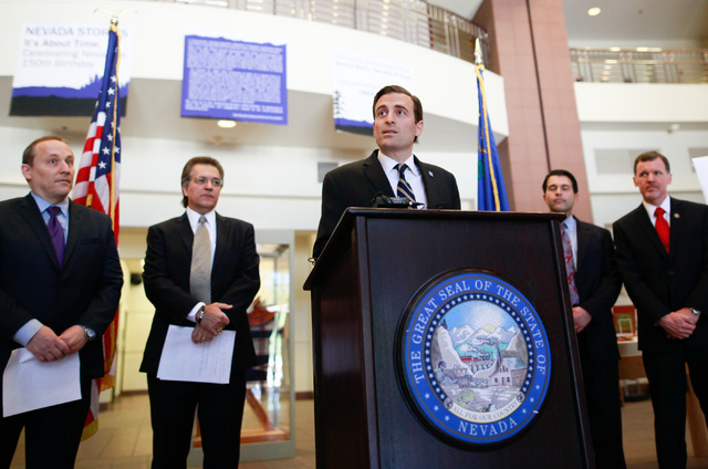 Nevada Attorney General Adam Laxalt, center, speaks with news media about the arrest warrant being issued for Bryan Micon, who ran an illegal poker site that was shut down, at the Sawyer Building  ...