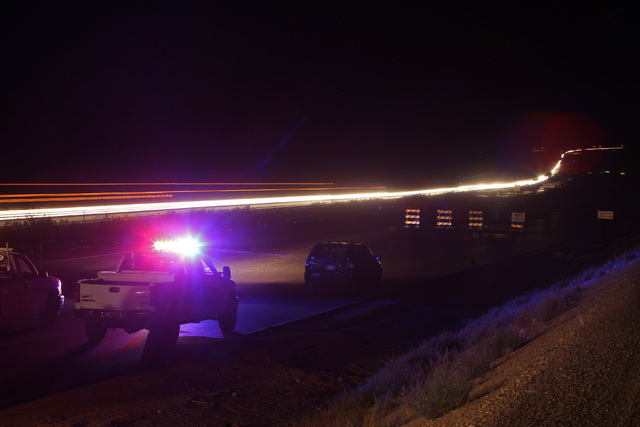 Southbound traffic is halted while northbound traffic streams towards Las Vegas while workers install a new sign over Interstate 15 near Yates Well Road south of Primm, Wednesday, June 17, 2015. S ...