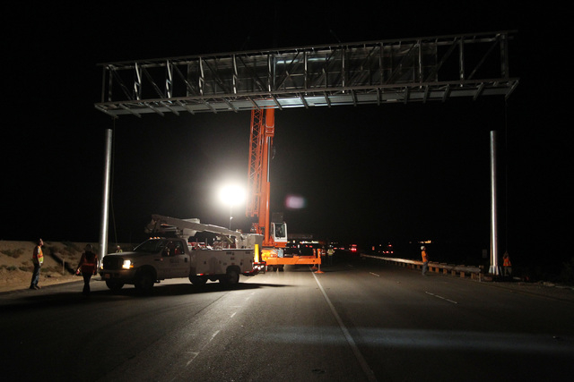 A crane lifts a sign into place while installing it over Interstate 15 near Yates Well Road south of Primm, Wednesday, June 17, 2015. Southbound traffic was stopped at Primm from 1 a.m. to about 4 ...