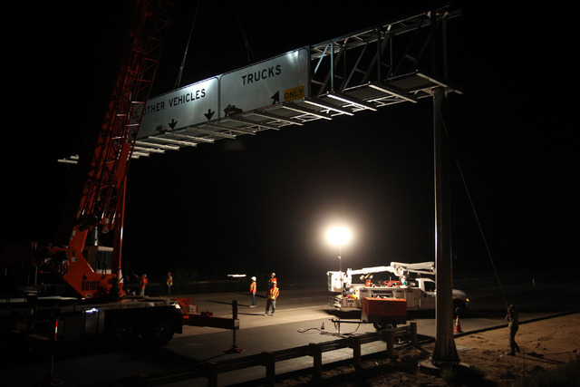 Workers from B C Traffic install a new sign over Interstate 15 near Yates Well Road south of Primm, Wednesday, June 17, 2015. Southbound traffic was stopped at Primm from 1 a.m. to about 4:30 a.m. ...
