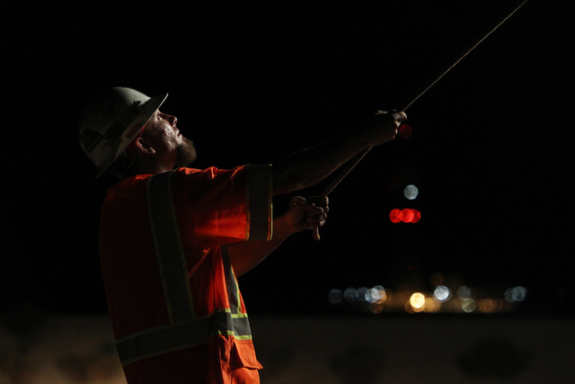 A worker from B C Traffic guides a sign into place while installing it over Interstate 15 near Yates Well Road south of Primm, Wednesday, June 17, 2015. Southbound traffic was stopped at Primm fro ...