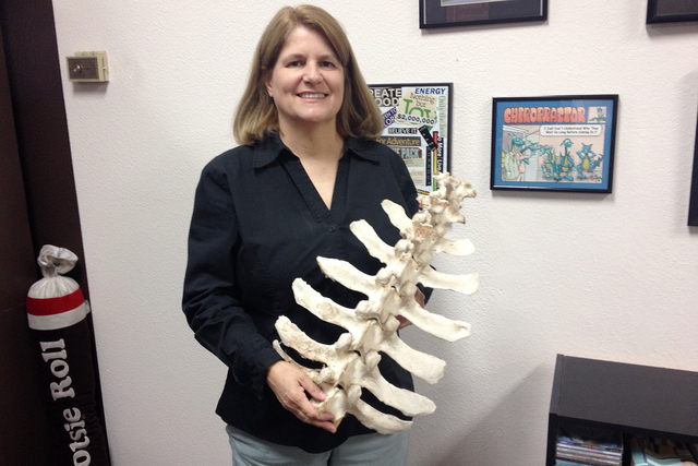 Chiropractor Dr. Brenda L. Hilby stands with a model of a spine. (Special to View)