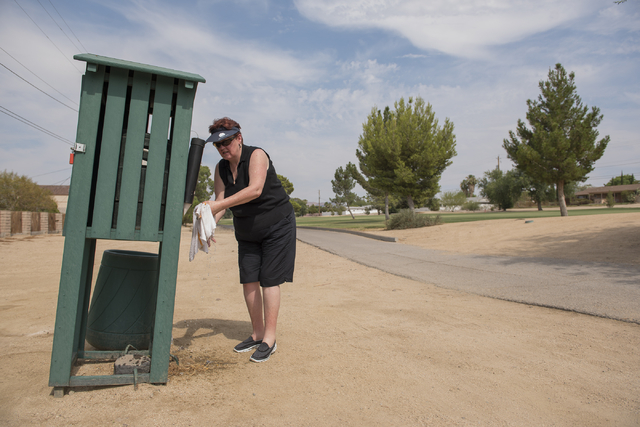 Diane Smith of El Paso, Texas, soaks a towel with cold water to stay cool from the heat during her round at Black Mountain golf course in Henderson on Friday, June 26, 2015. (Martin S. Fuentes/Las ...