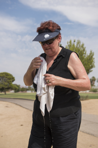 Diane Smith of El Paso, Texas, wipes herself with a cold wet towel to stay cool from the heat during her round at Black Mountain golf course in Henderson on Friday, June 26, 2015. (Martin S. Fuent ...