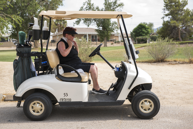 Diane Smith of El Paso, Texas, places a cold wet towel over her neck to stay cool from the heat during her round at Black Mountain golf course in Henderson on Friday, June 26, 2015. (Martin S. Fue ...